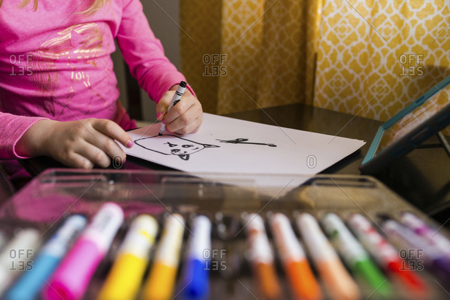 Midsection of girl drawing on paper at home