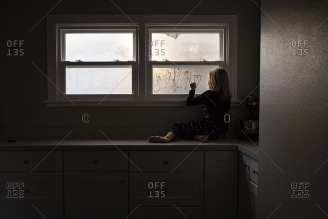 Girl making heart shape on condensed window while sitting on kitchen counter at home