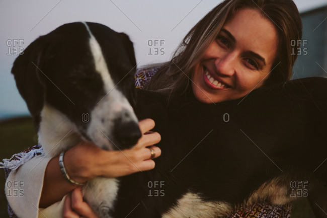 Portrait of happy woman embracing dog outdoors
