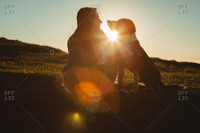 Woman and dog looking at each other while sitting on hill during sunset