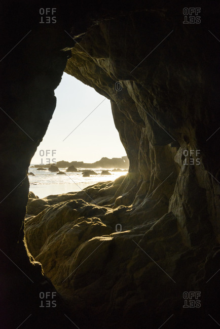 Beach seen through cave during sunny day