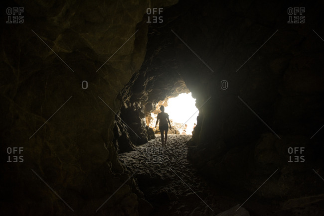 Rear view of woman walking in cave