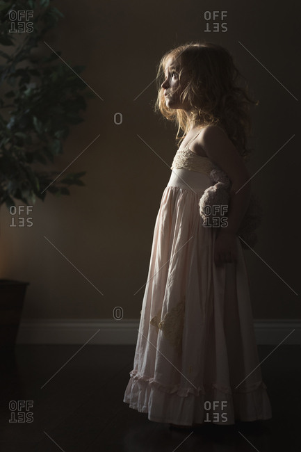 Side view of thoughtful girl holding teddy bear while standing at home