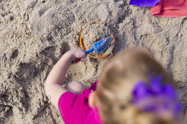 Overhead view of girl playing with sand at beach