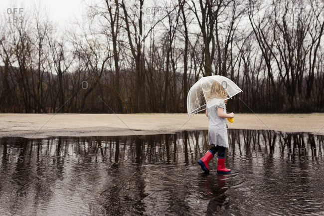 Side view of girl carrying umbrella while walking on puddle during rainy season