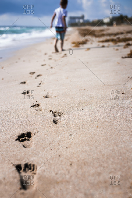 Rear view of boy leaving behind footprints while walking on sand at beach