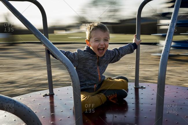 Portrait of cheerful boy sitting on merry-go-round