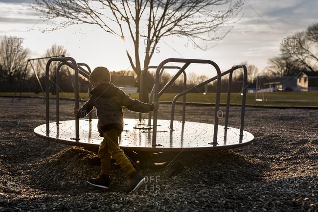 Boy spinning merry-go-round at playground