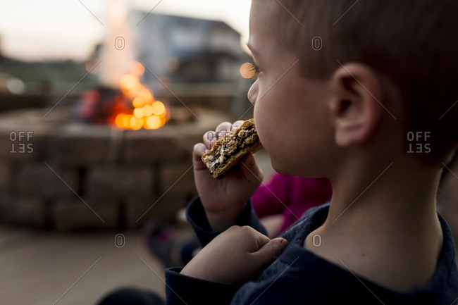 Boy eating smore at yard with fire pit in background