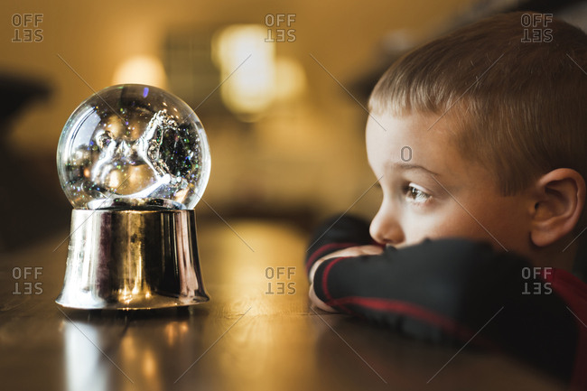 Side view of boy looking at snow globe