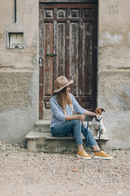 Woman looking at Jack Russell Terrier while sitting on front stoop