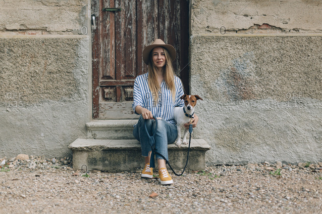Portrait of woman with Jack Russell Terrier sitting on front stoop