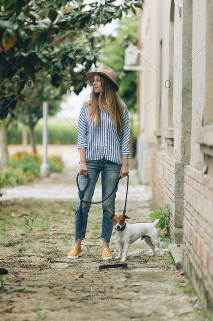 Full length of woman with Jack Russell Terrier standing by house