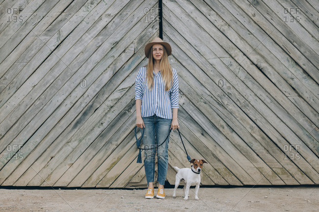 Portrait of woman with Jack Russell Terrier standing against wooden gate