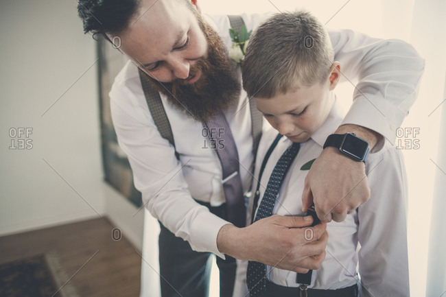 Bridegroom assisting pageboy in getting dressed at home