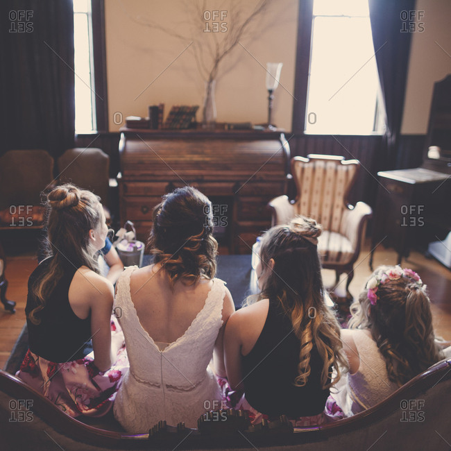 Rear view of bride with bridesmaids and flower girl sitting on sofa at home