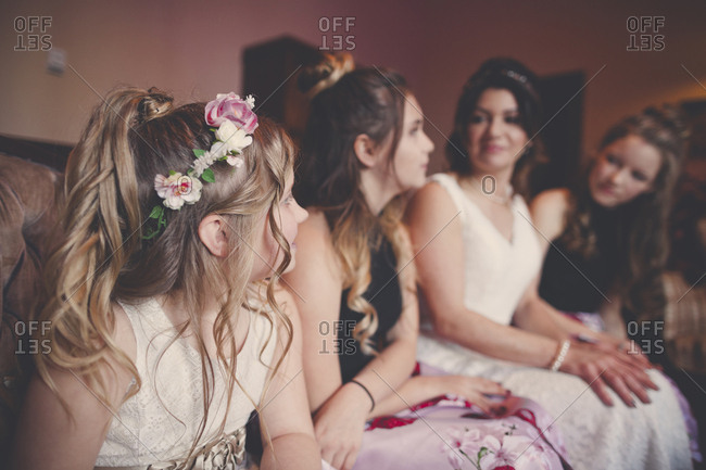 Bride with bridesmaids and flower girl sitting at home