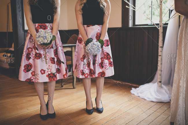 Low section of bridesmaids holding bouquets while standing at home