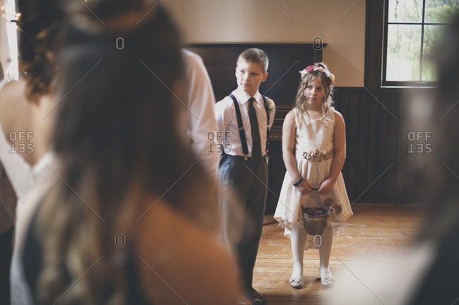 Flower girl with pageboy looking at bride during wedding ceremony