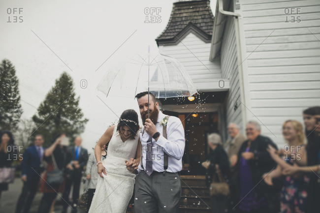 People looking at happy newlywed couple walking with umbrella during snowfall