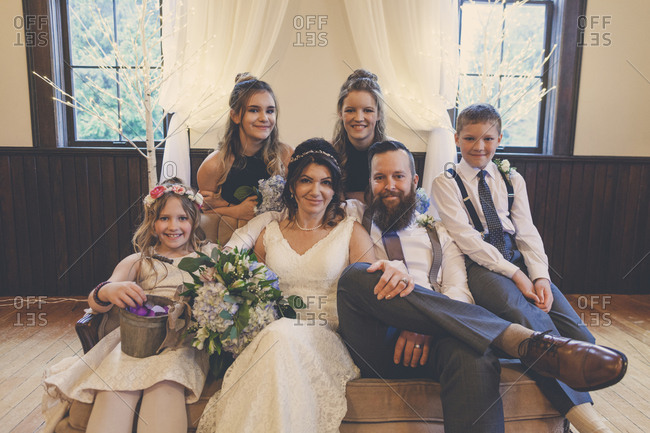 Portrait of newlywed couple sitting by pageboy and flower girl with bridesmaids on sofa during wedding ceremony