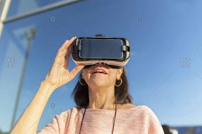 Woman using VR glasses while standing against building