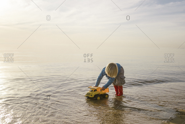 Boy playing with toy truck in sea against cloudy sky during sunset