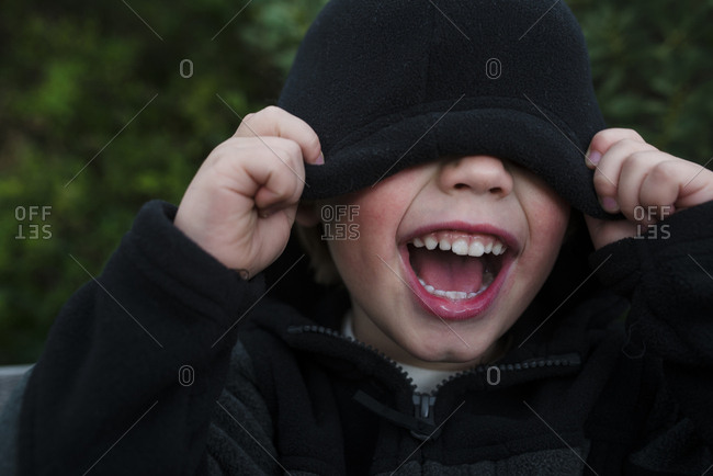 Boy screaming while covering eyes with hooded shirt