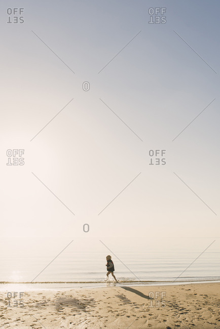 Side view of boy wearing life jacket running in sea during foggy weather