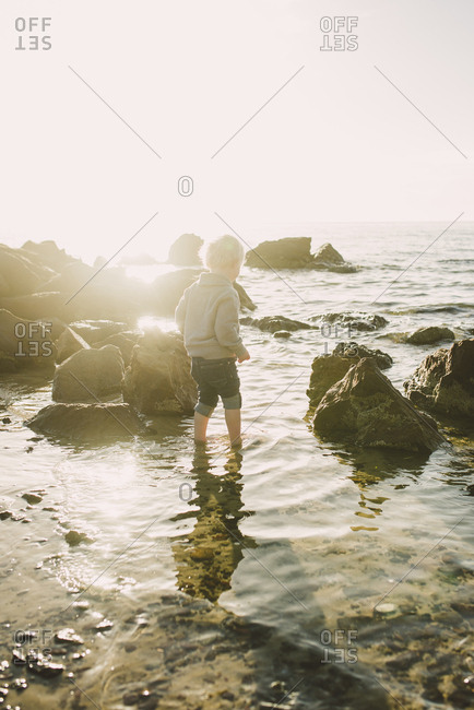 Rear view of boy standing in sea against sky during sunny day