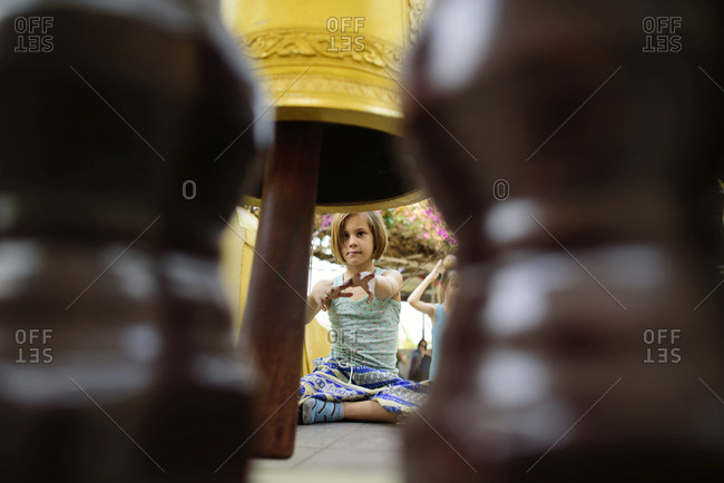 Girl gesturing while sitting by prayer bell in temple seen through railing