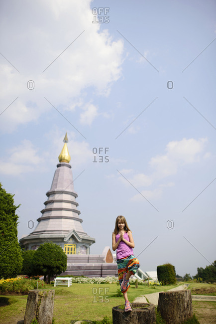 Girl standing in tree pose against pagoda at Doi Inthanon National Park