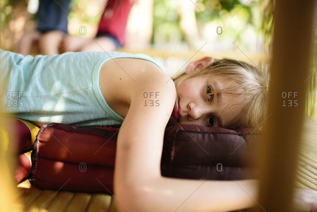 Portrait of girl lying on pillow at porch