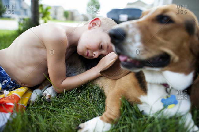 Boy leaning on beagle at grassy field