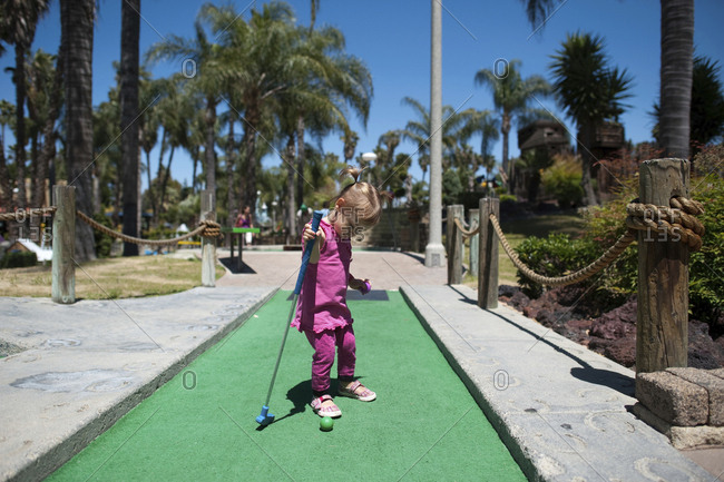 Full length of girl playing miniature golf on sunny day