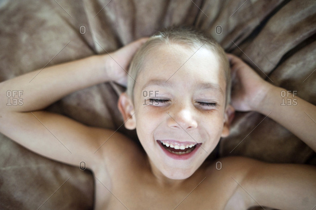 Overhead view of boy lying on bed at home