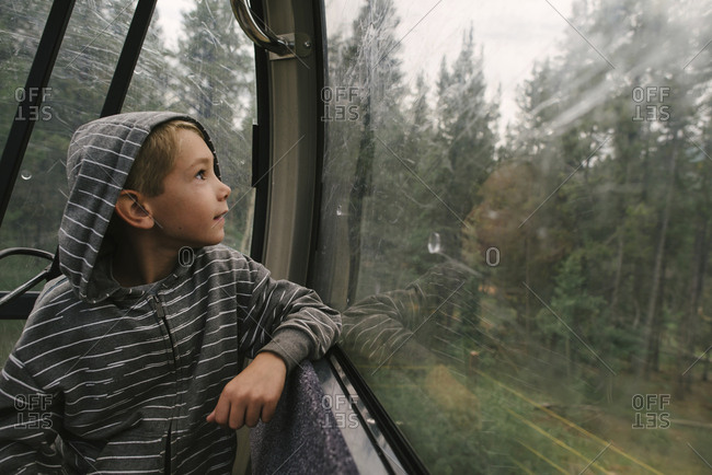 Boy looking through window while traveling in overhead cable car