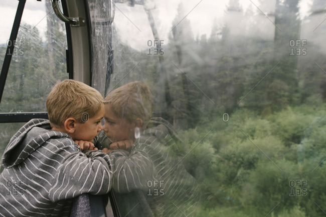 Side view of boy looking through window while traveling in overhead cable car