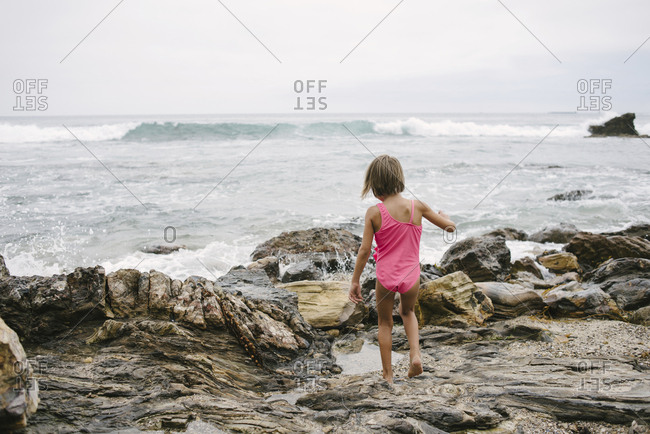 Rear view of girl walking on rocks at beach against sky