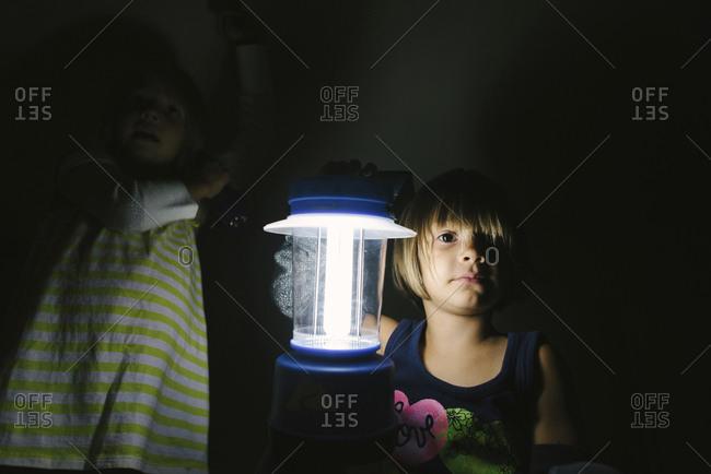 Portrait of girl holding illuminated electric lamp in darkroom