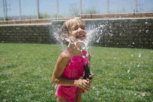 Cheerful girl splashing water on face with garden hose