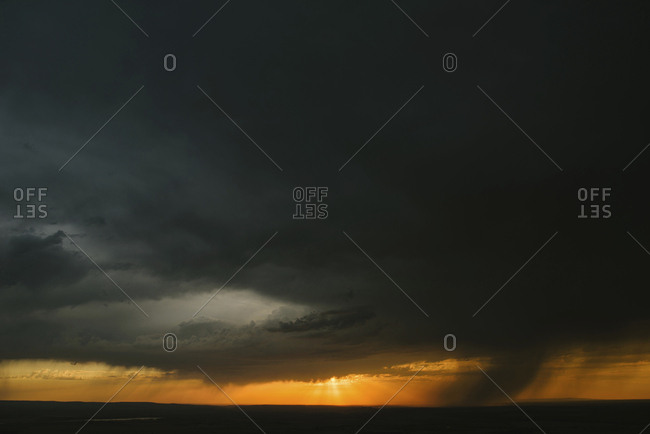 Silhouette landscape against cloudy sky during sunset