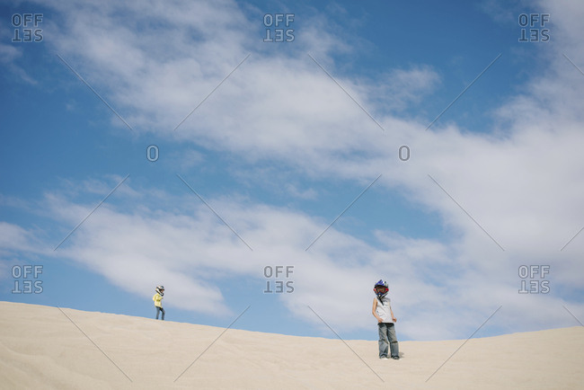 Low angle view of siblings wearing crash helmets while standing on sand at beach