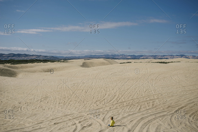 High angle view of girl kneeling on sand against sky