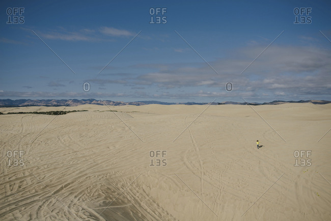 Distant view of girl running on sand against sky