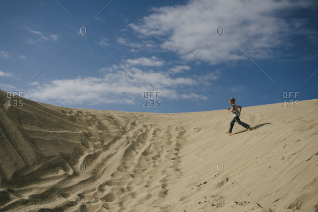 Side view of boy running on sand at beach