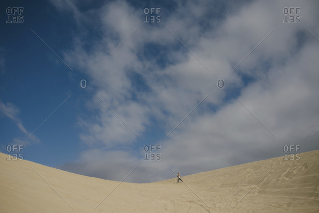 Distant view of boy running on sand against blue sky