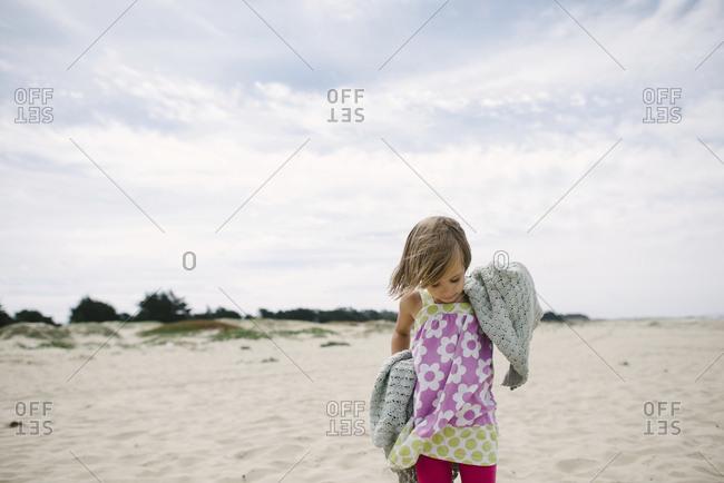 Girl standing on sand at beach against sky