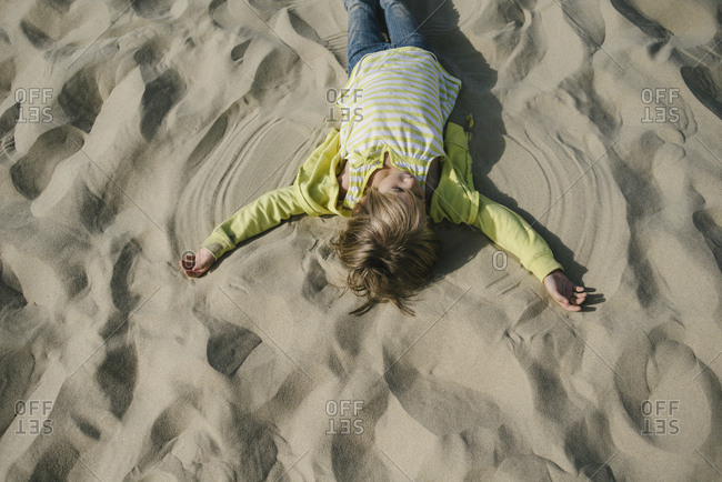 Overhead view of girl making sand angel at beach