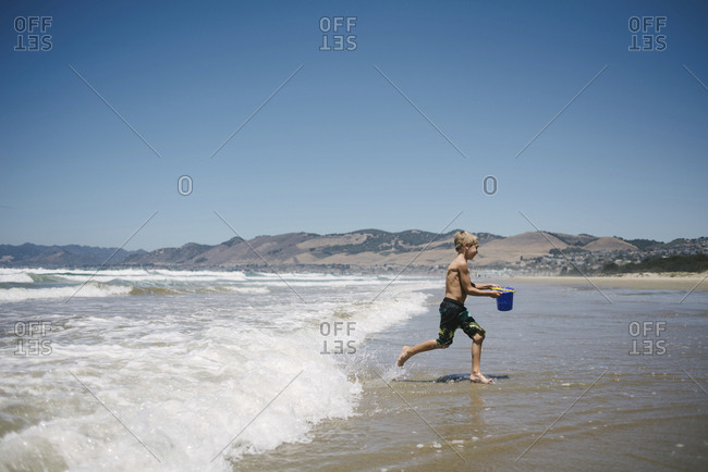 Side view of boy carrying water in bucket while running on shore at beach